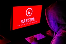 Computer screen with ransomware attack alerts in red and a hacker man keying on keyboard in a dark room, ideal for online security failure and digital crime