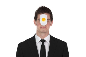 Businessman with egg on face
